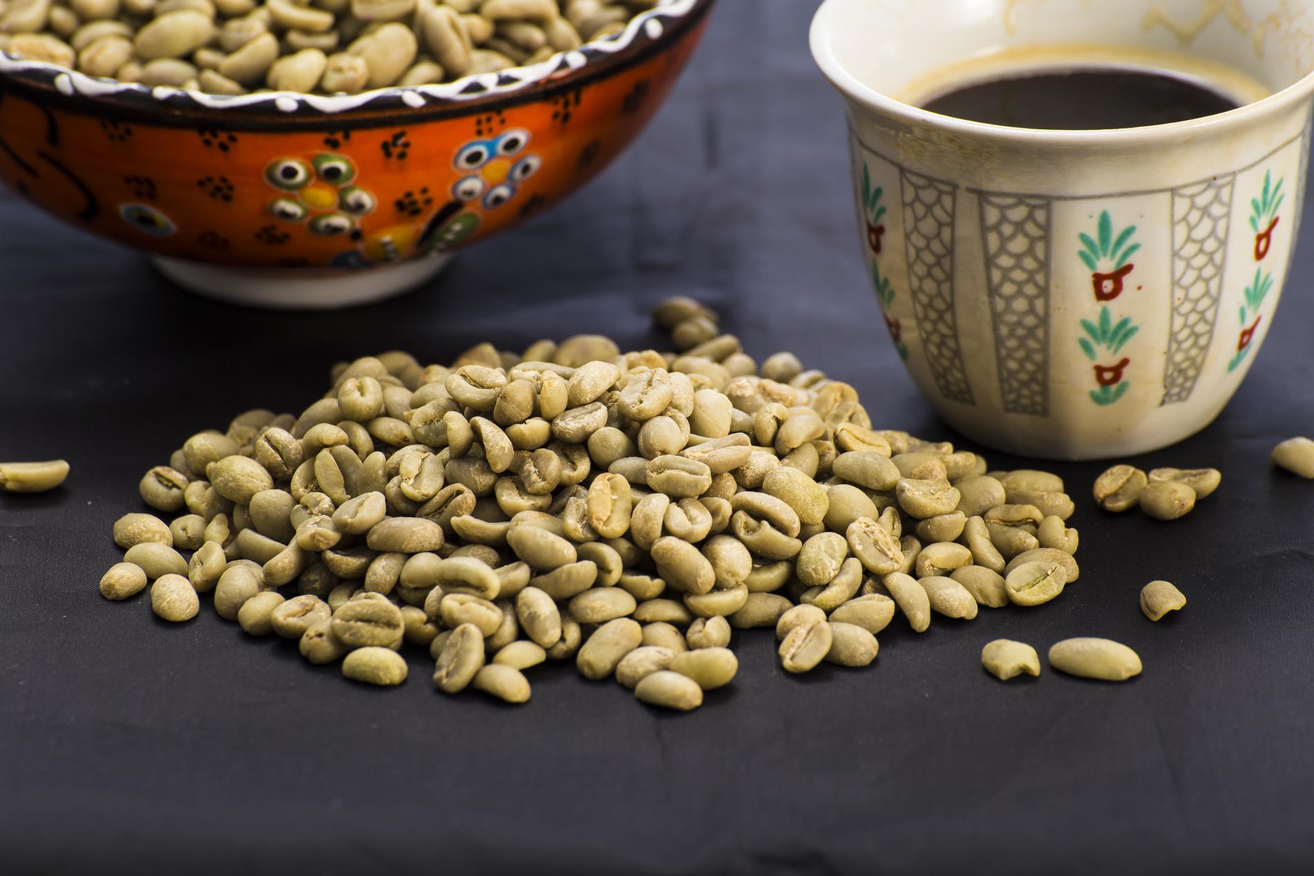 Foto mit Schale voll Kaffeebohnen, lose Kaffeebohnen und ein Tässchen Kaffee