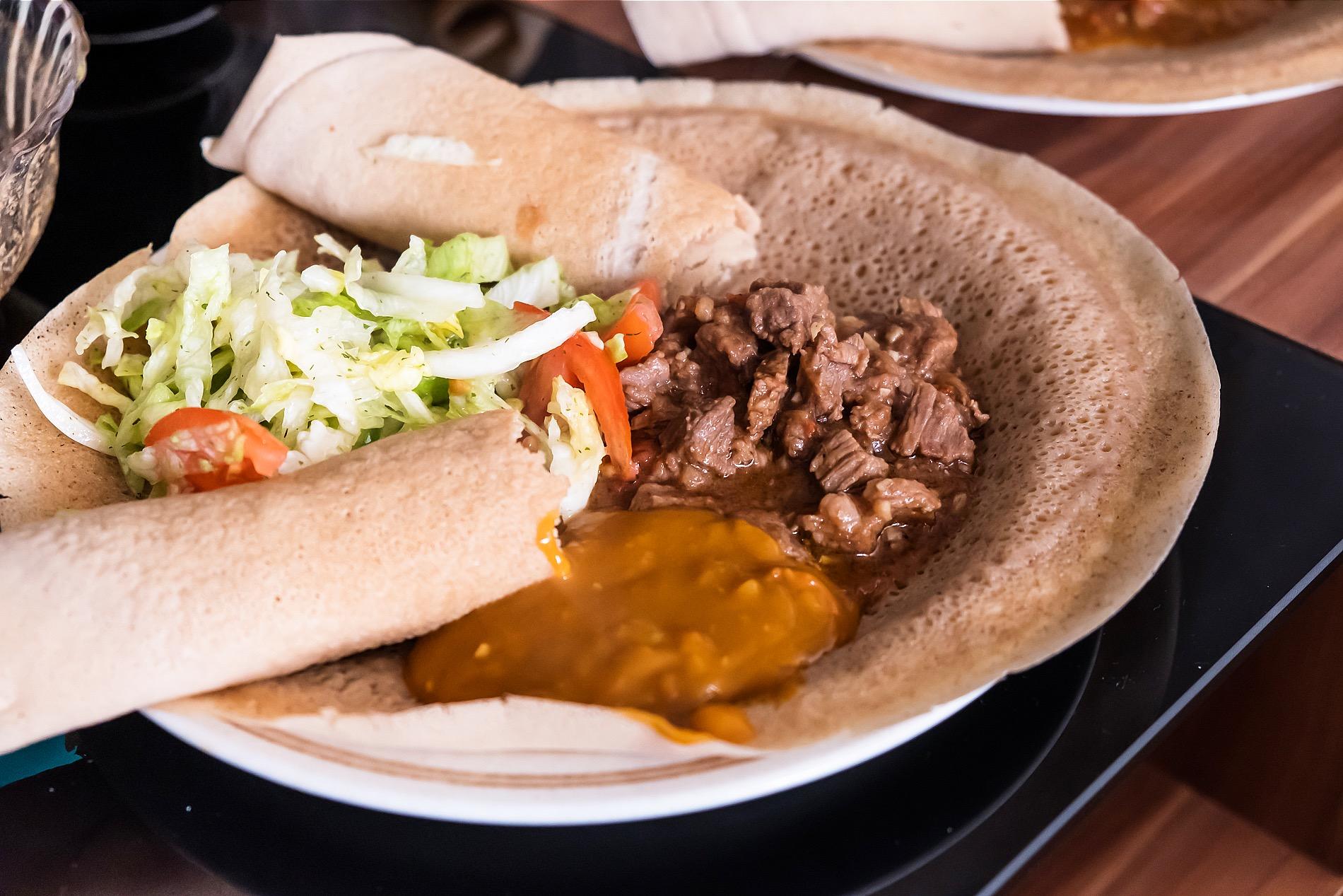 Foto mit angerichtetem Teller mit Fladen, Salat und Fleisch