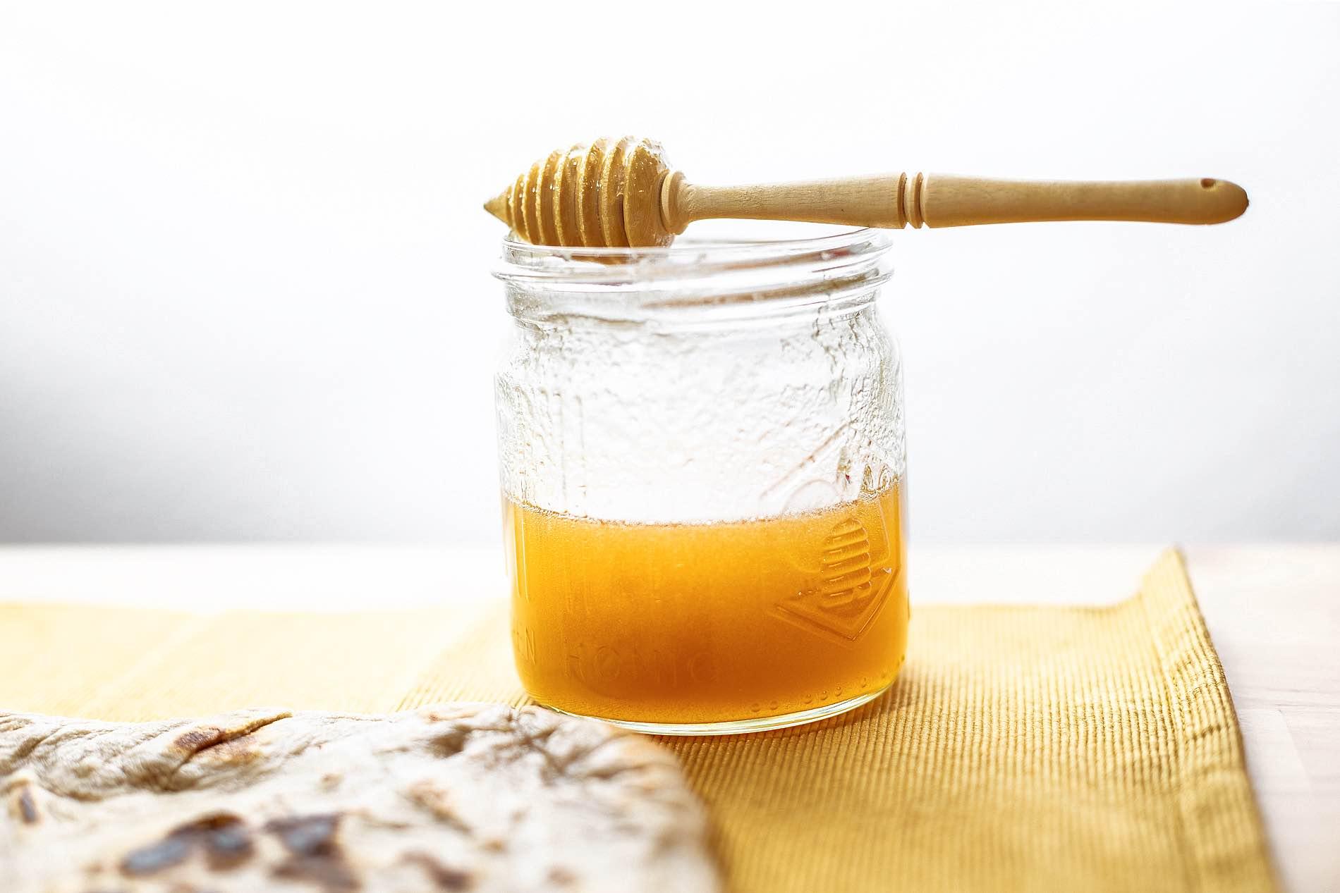 Foto eines Honigglases auf dem ein Honiglöffel liegt