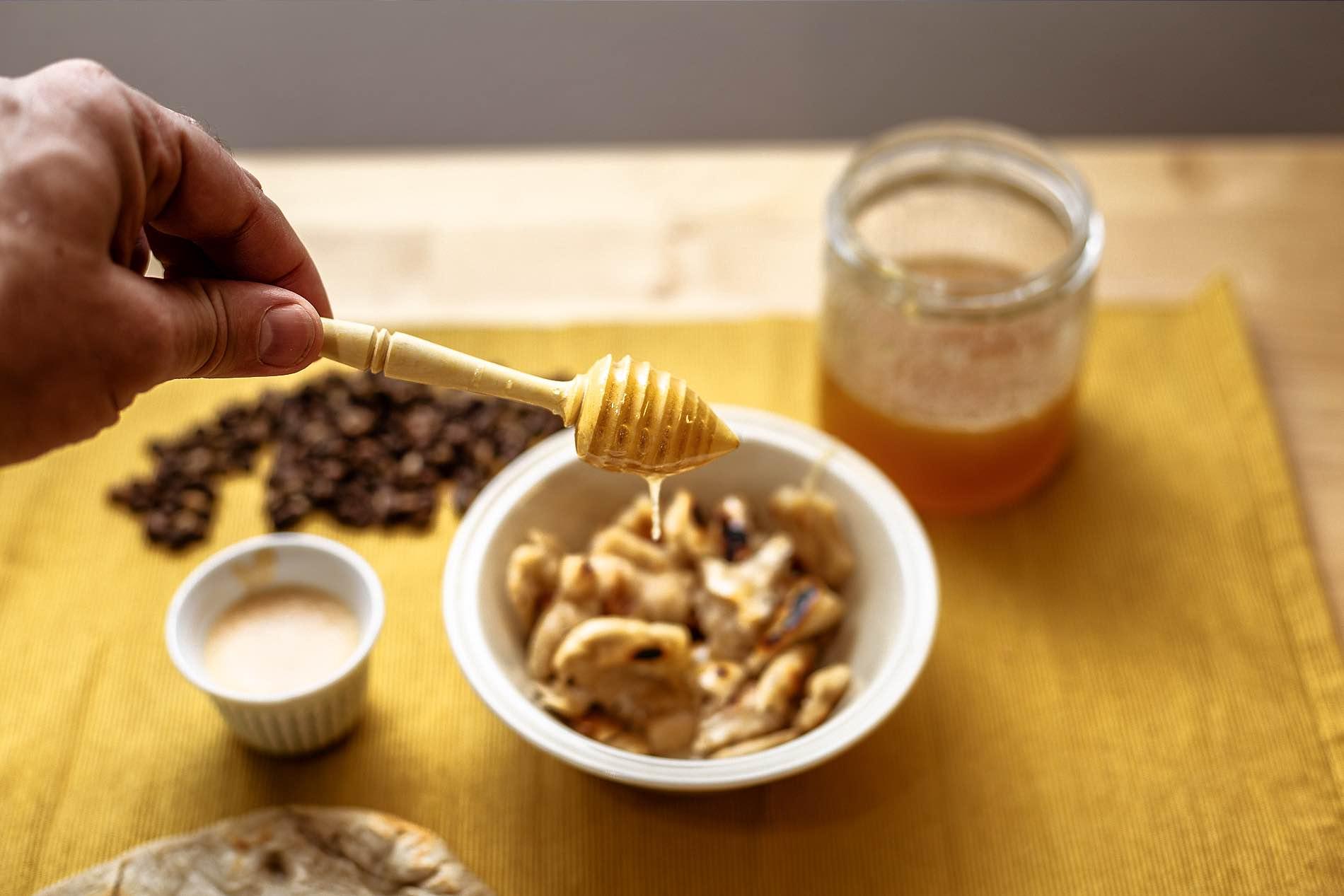 Foto einer Hand, die einen Honiglöffel hält von dem Honig tropft