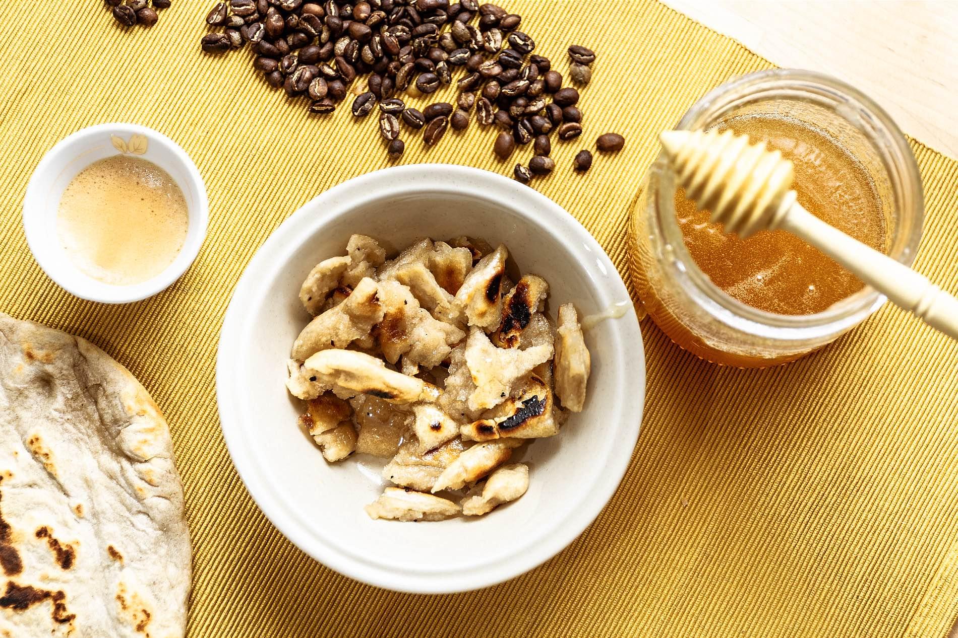 Foto einer kleinen Schüssel mit Brotstückchen, daneben ein Glas Honig